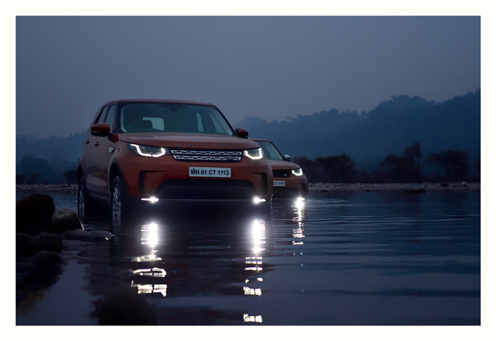 Land Rover Discoverys crossing a river outside Namdhapa. Evening.
